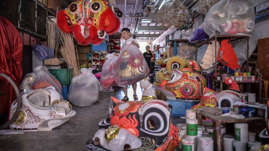 Wong then puts the completed lion heads to one side, while waiting for customers to come and pick up the lion head. Here, he is wrapping the lion head with a plastic cover. ADIB RAWI YAHYA/THESUN