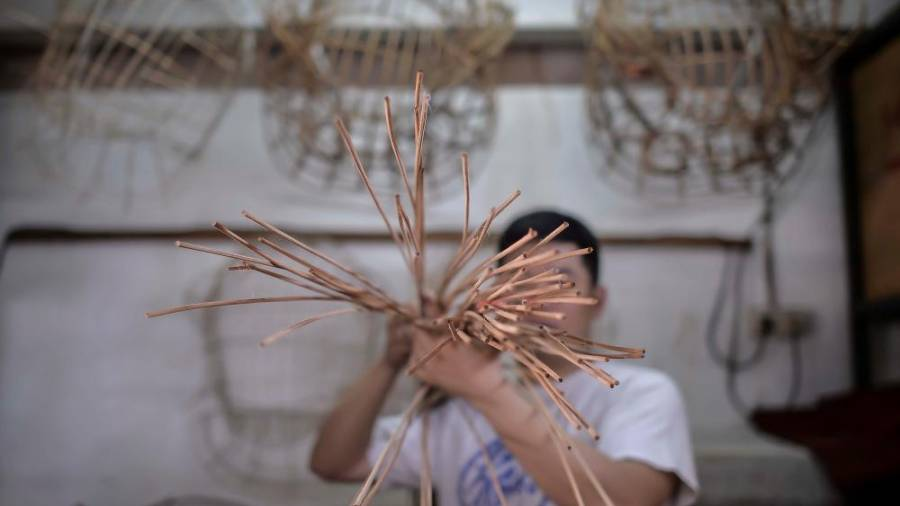 Wan Seng Hang supervisor Wong Siong Loong shows the process by feeding rattan stems through a special cutting tool to produce slimmer pieces. ADIB RAWI YAHYA/THESUN