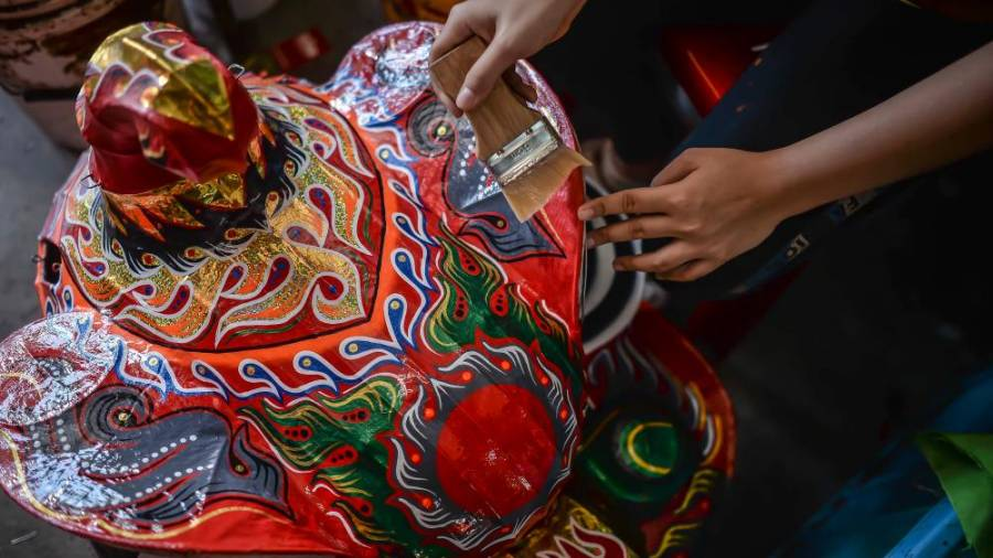 Once the paint has dried, a worker then applies lacquer onto the lion head to ensure that there is a protective layer and the colours stay vibrant and shiny for a long time. ADIB RAWI YAHYA/THESUN