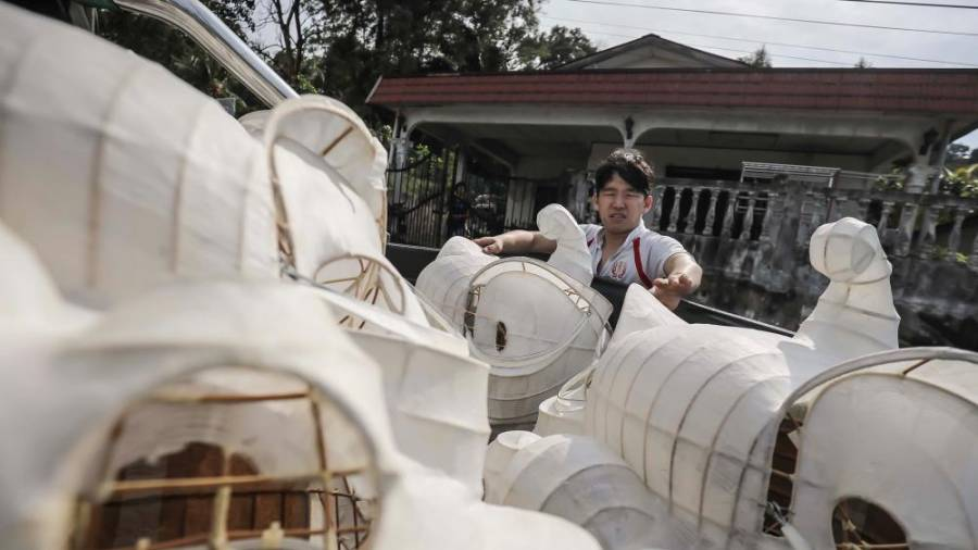 A Wan Seng Hang worker takes the lion head frames that has been applied with white bamboo paper from the woman's house using a pick-up truck. ADIB RAWI YAHYA/THESUN