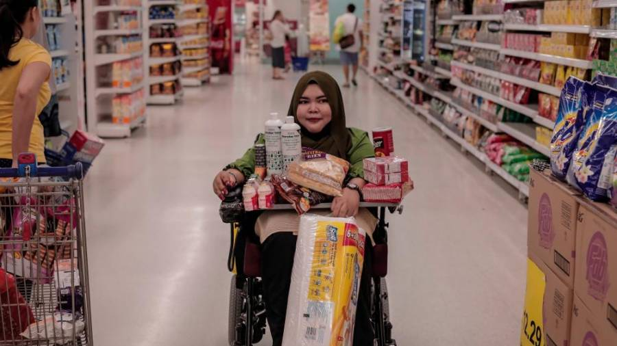 Navigating her motorised wheelchair though the many aisles, Nur Fazira shops for groceries and business supplies.