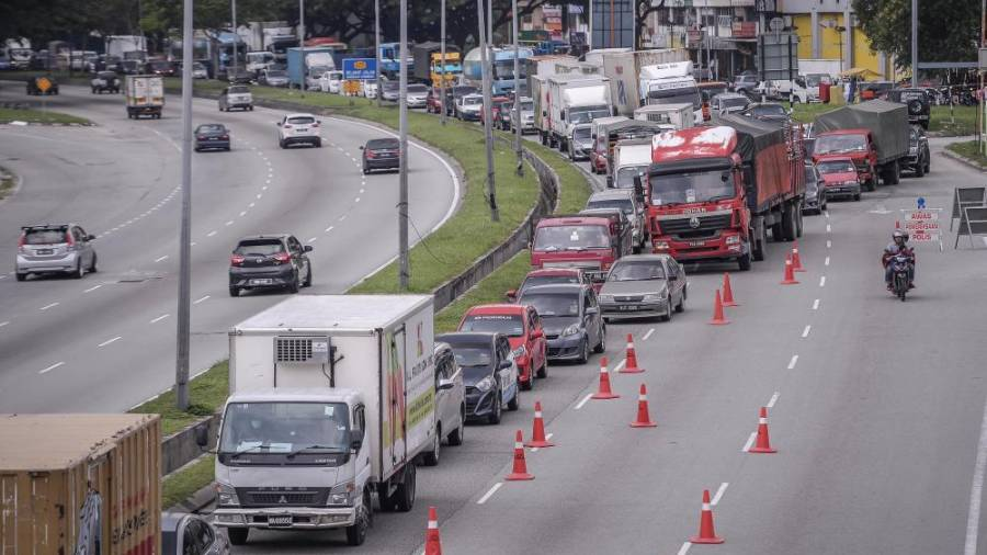 FIRST DAY of CMCO ... Traffic backed up on Jalan Kuching in Kuala Lumpur yesterday due to roadblocks set up to ensure adherence to the conditional movement control order. – ADIB RAWI YAHYA/THESUN