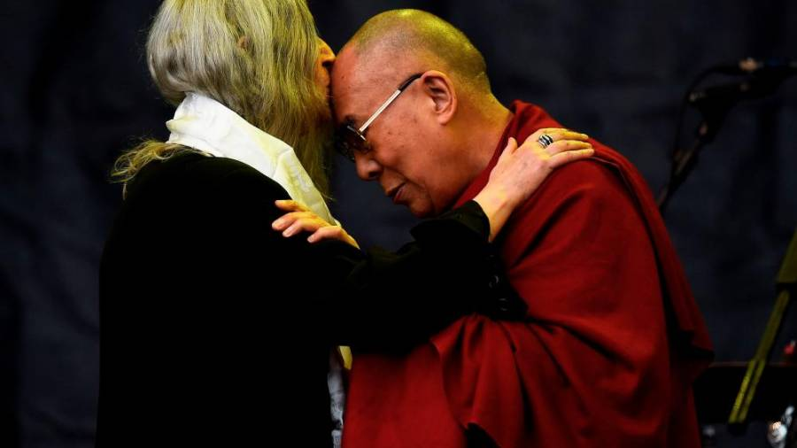 Patti Smith kisses the Dalai Lama as she performs on the Pyramid stage at Worthy Farm in Somerset during the Glastonbury Festival in Britain, June 28, 2015. REUTERS/Dylan Martinez/File Photo