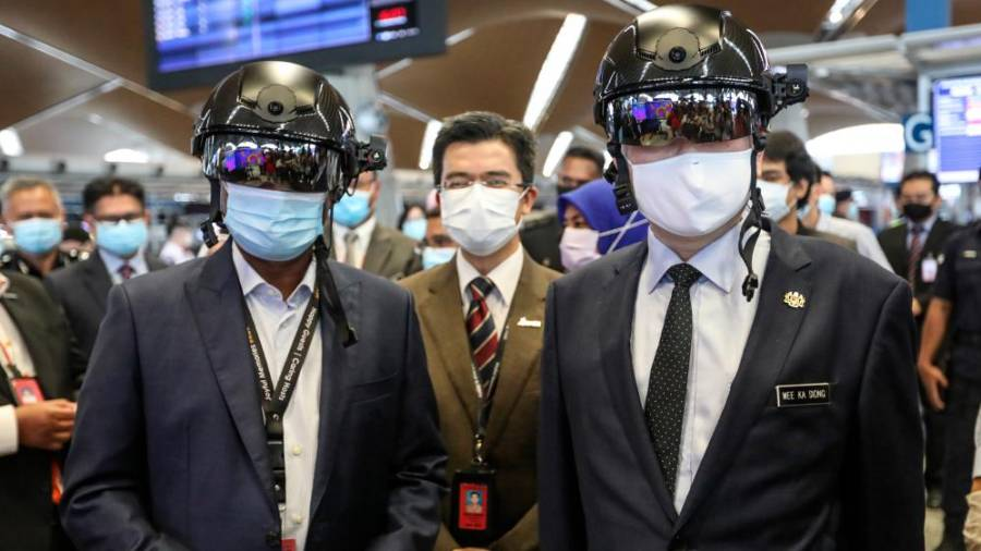 SMART HEADGEAR ... Transport Minister Datuk Seri Wee Ka Siong (right) and Malaysia Airport Holdings Bhd chairman Datuk Seri Zambry Abdul Kadir try out the Robocop-style helmet that can detect body temperatures, after launching the shopMYairports eCommerce platform at KL International Airport yesterday. – ASHRAF SHAMSUL/THESUN