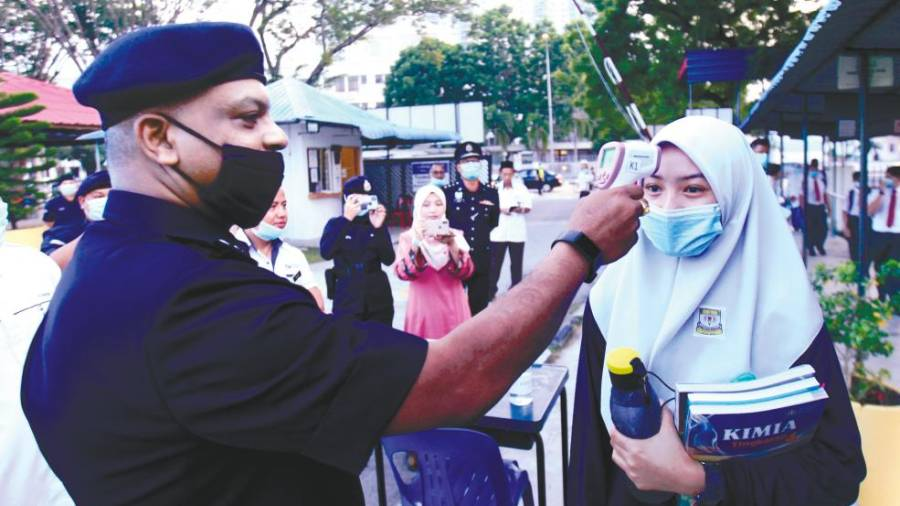 Balik Pulau OCPD Supt A. Anbalagan checking the temperature of a student at SM Raja Tun Uda in Penang yesterday. – MASRY CHE ANI/THESUN
