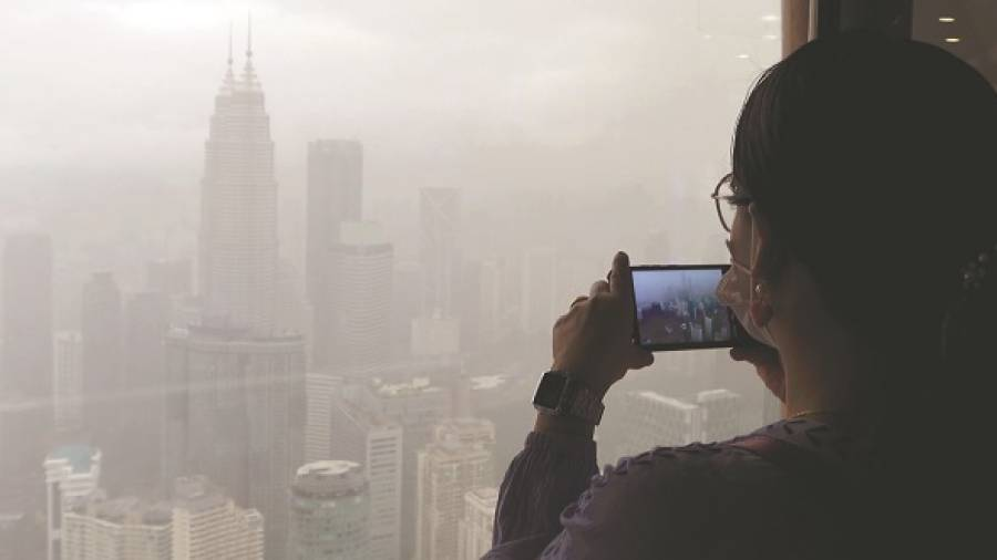 SMOKY VISION ... A visitor taking pictures of the city skyline at the KL Tower yesterday under rainy and hazy conditions. – ZAHID IZZANI/THESUN