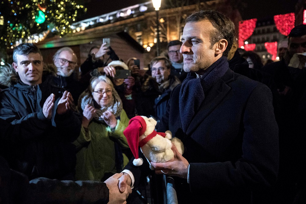 French President Emmanuel Macron receives a gift from a visitor as he visits the Christmas market in Strasbourg Dec 14, 2018. — Reuters