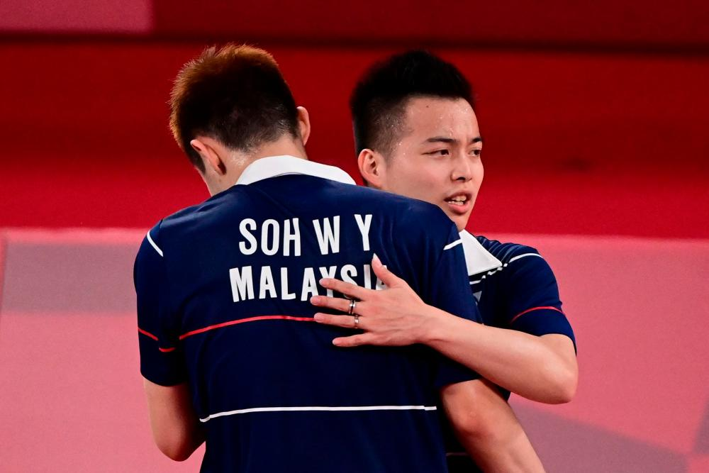 Malaysia's Soh Wooi Yik (L) and Malaysia's Aaron Chia hug after winning their men's doubles badminton quarter final match against Indonesia's Kevin Sanjaya Sukamuljo and Indonesia's Marcus Fernaldi Gideon during the Tokyo 2020 Olympic Games at the Musashino Forest Sports Plaza in Tokyo on July 29, 2021. AFPPIX