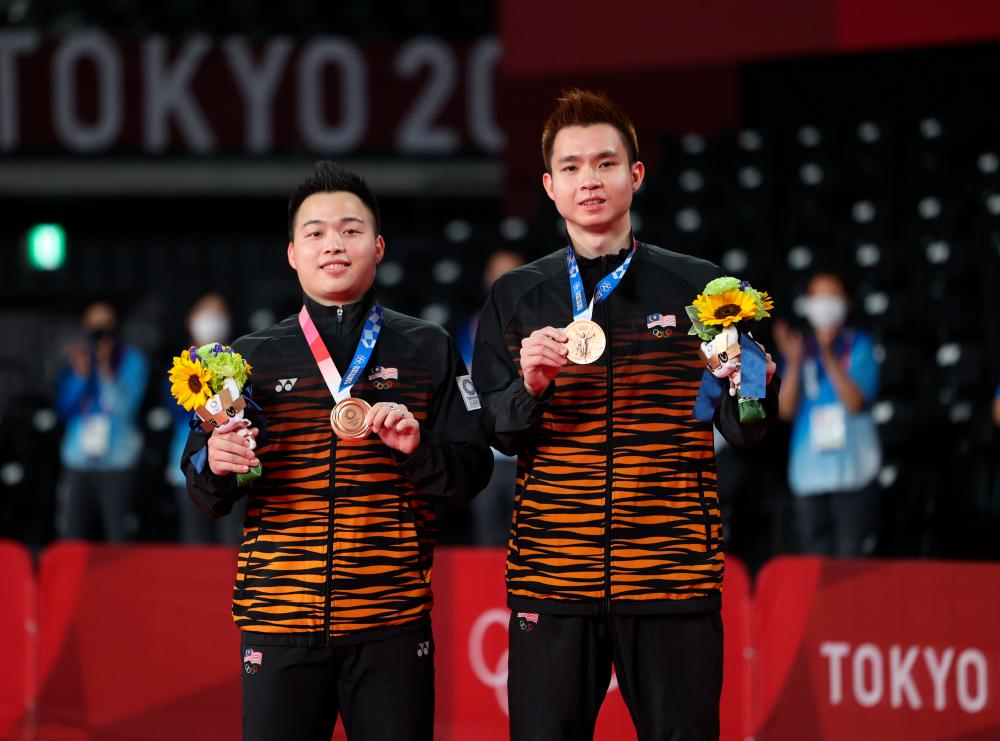 National men's badminton duo Aaron Chia (right) and Soh Wooi Yik (left) posing with the first bronze medal that they won after beating the Indonesian team at the Tokyo 2020 Olympic Games at Mushashino Sports Plaza today. — Bernama