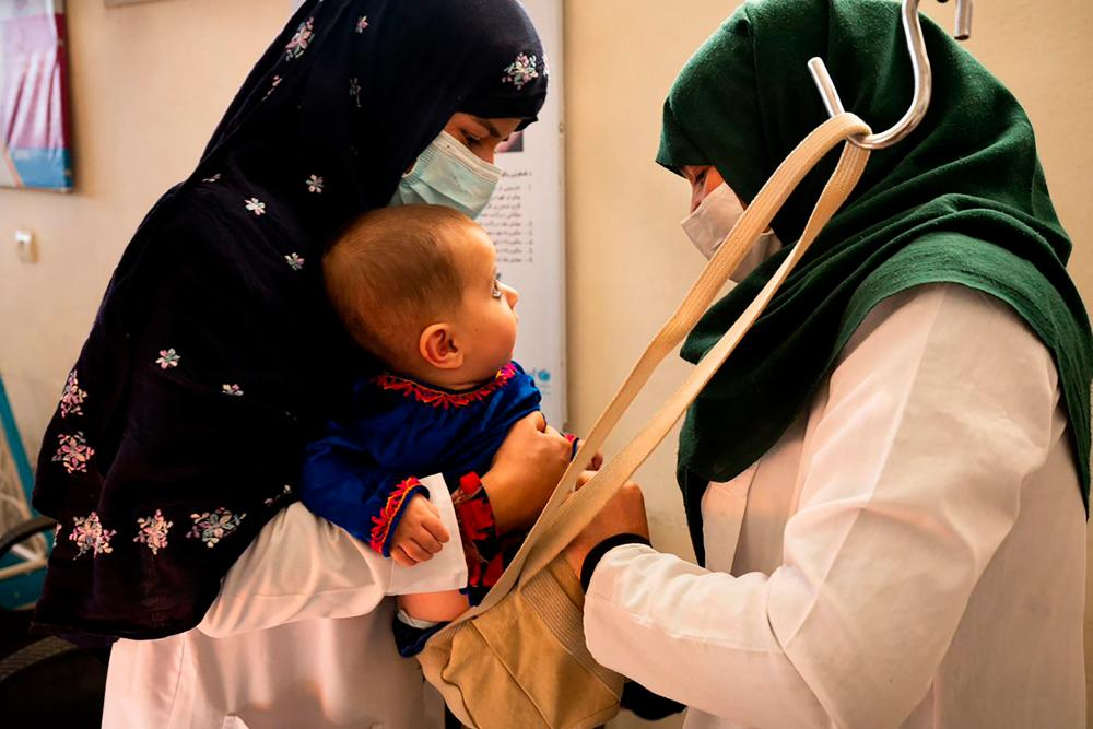 This picture taken on October 6, 2021 shows a midwife (L) and a nutrition counsellor weighing a baby at the Tangi Saidan clinic run by the Swedish Committee for Afghanistan, in Daymirdad district of Wardak province.AFPpix