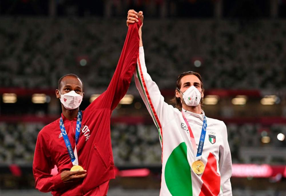 Qatar's Mutaz Essa Barshim and Italy's Gianmarco Tamberi sharing the top spot on the podium for the men's high jump at the 2020 Tokyo Olympic Games. – AFP