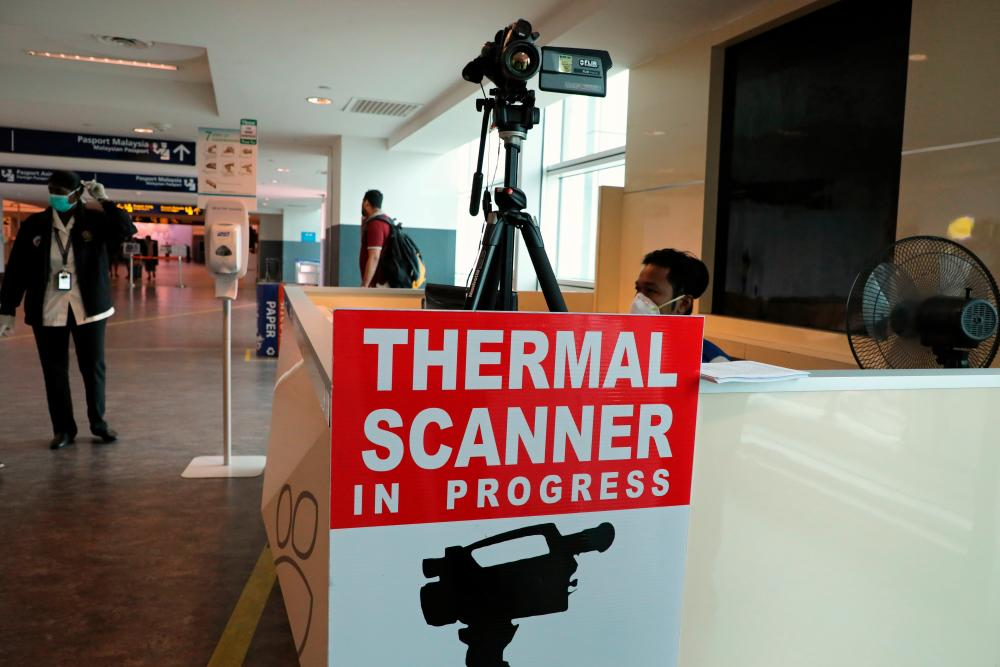 A health quarantine officer waits for passengers at a thermal screening point at the international arrival terminal of Kuala Lumpur International Airport 2 in Sepang, January 27, 2020. - Reuters