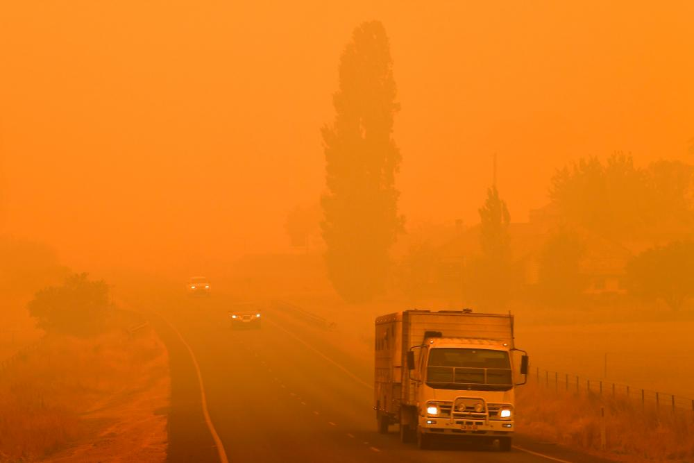 Residents commute on a road through thick smoke from bushfires in Bemboka, in Australia's New South Wales state on January 5, 2020. - AFP