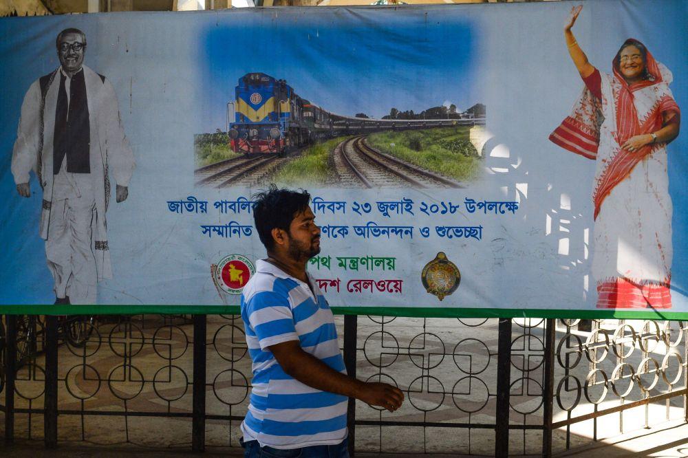 A Bangladeshi man walks past a poster with the images of Sheikh Mujibur Rahman (L), founding father of Bangladesh, and Bangladeshi Prime Minister Sheikh Hasina at Kamalapur railway station in the Bangladeshi capital Dhaka Jan 1, 2019. — AFP