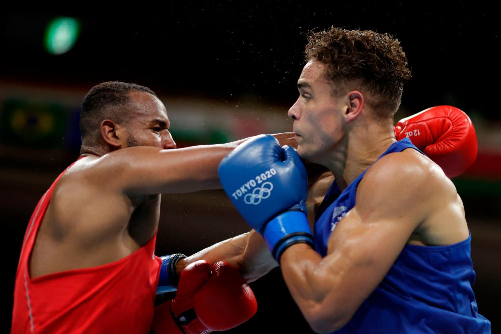 Morocco's Youness Baalla (red) and New Zealand's David Nyika fight during their men's heavy (81-91kg) preliminaries round of 16 boxing match during the Tokyo 2020 Olympic Games at the Kokugikan Arena in Tokyo on July 27, 2021. -AFP