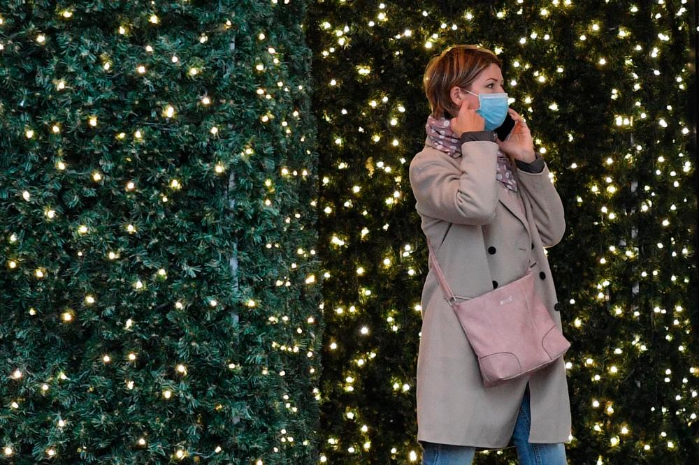 A woman walks past a Christmas light display at a department store in central London on Thursday. – AFPPIX