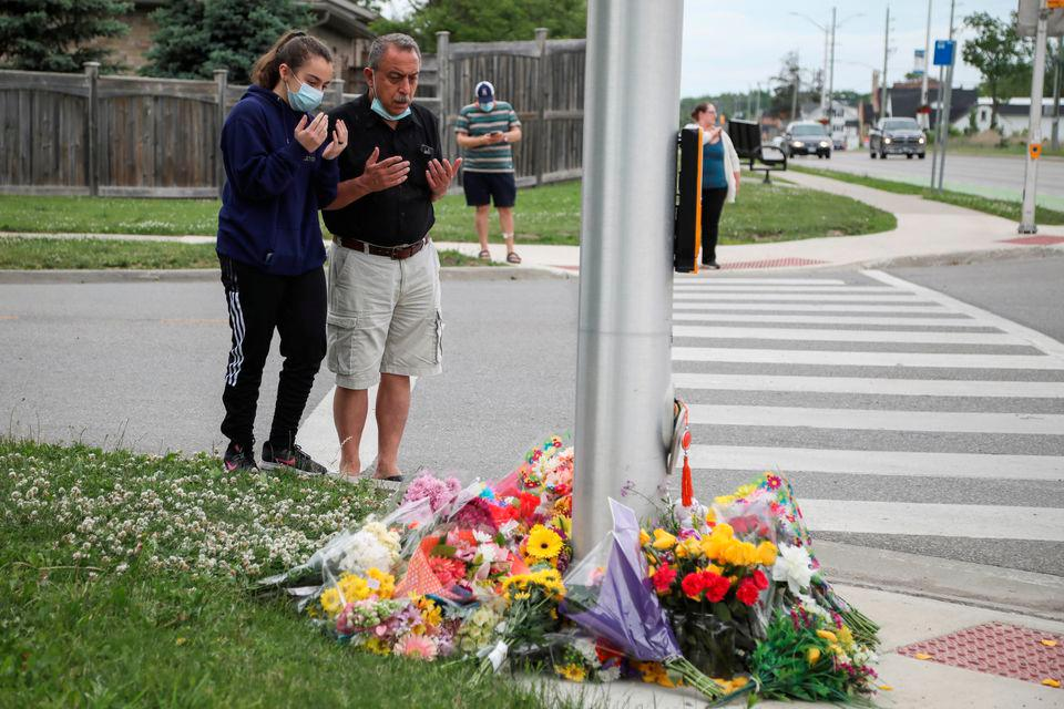 Abdullah Alzureiqi and his daughter Hala say a prayer at the fatal crime scene where a man driving a pickup truck jumped the curb and ran over a Muslim family in what police say was a deliberately targeted anti-Islamic hate crime, in London, Ontario, Canada June 7, 2021. — Reuters