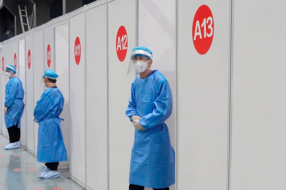 Staff members wait outside booths where people receive a vaccine against the coronavirus disease (Covid-19) at a vaccination center, during a government-organized visit, in Beijing, China, April 15, 2021. REUTERSpix