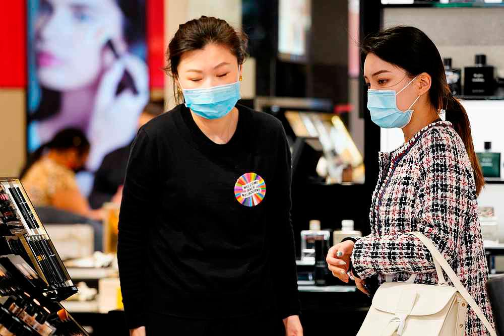 A shopper wearing a face mask is assisted in a retail store after Covid-19 restrictions were eased for the state of Victoria, in Melbourne, Australia October 28, 2020. — Reuters