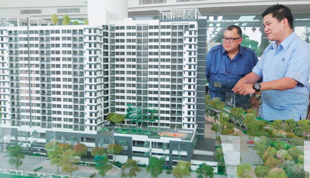 Yong (right) with a scale model of one of Crest Builder's projects. - Zulkifli Ersal/THE SUN