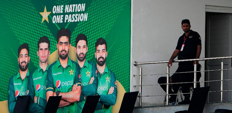A policeman stands guard next to a poster featuring Pakistan's cricket players at the Rawalpindi Cricket Stadium. – AFPPIX
