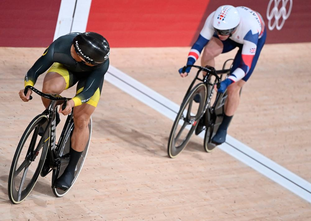 Britain's Jason Kenny (right) and Malaysia's Mohd Azizulhasni Awang compete in a heat of the men's track cycling sprint 1/32 finals during the Tokyo 2020 Olympic Games at Izu Velodrome in Izu, Japan. – AFPPIX