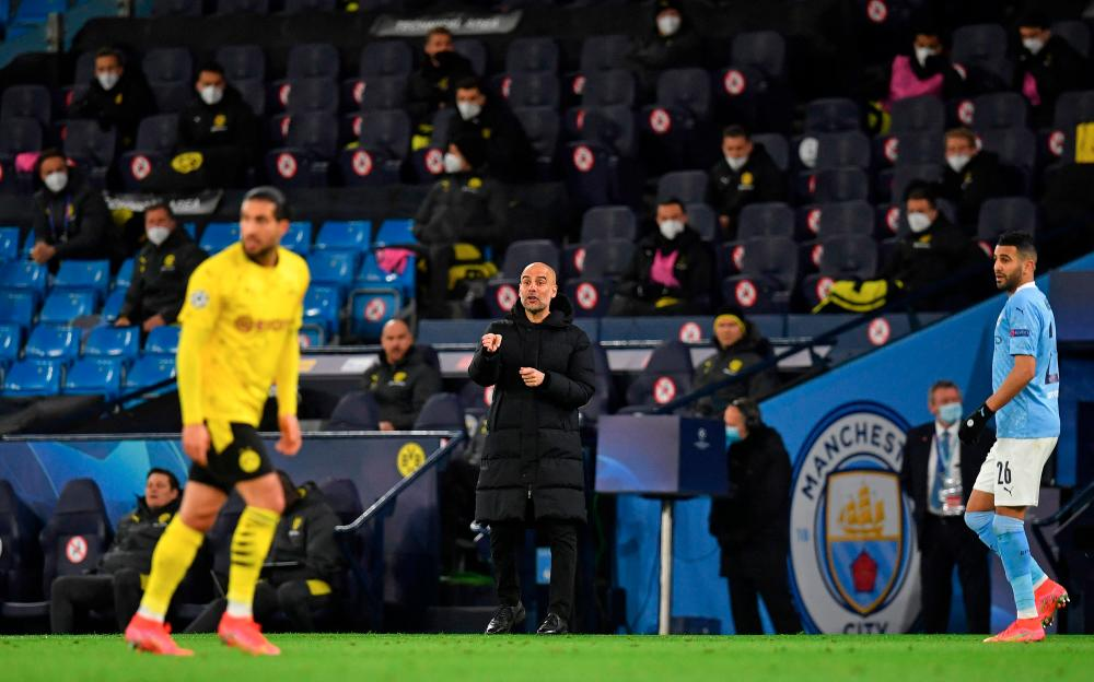Man City's manager Pep Guardiola (centre) shouts instructions to his players from the touchline during the UEFA Champions League first leg quarterfinal match against Borussia Dortmund at the Etihad Stadium. – REUTERSPIX