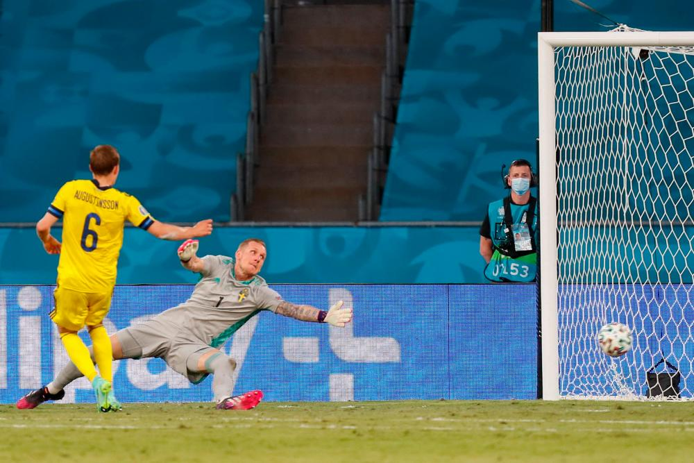 Sweden's goalkeeper Robin Olsen (back) eyes the ball passing in front of his goal during the UEFA EURO 2020 Group E match at La Cartuja Stadium in Sevilla this morning. – AFPPIX