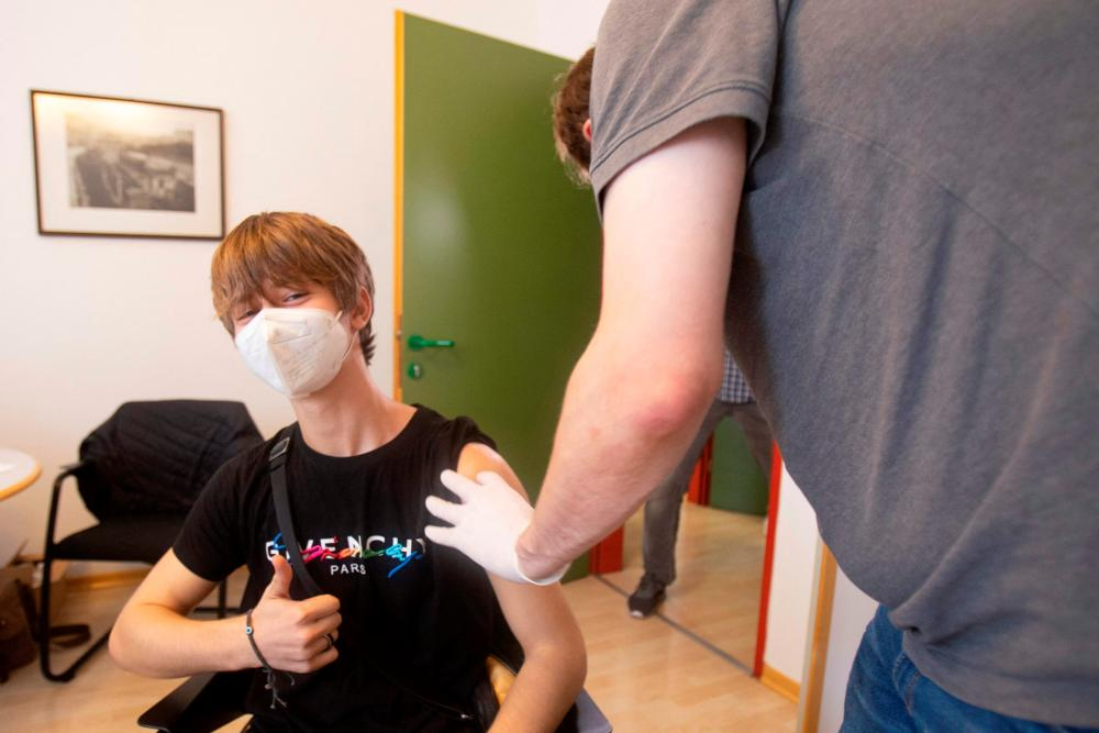 (FILES) In this file photo taken on September 14, 2021 a student is vaccinated against the coronavirus (Covid-19) at a vocational school in Vienna on September 14, 2021. AFPpix