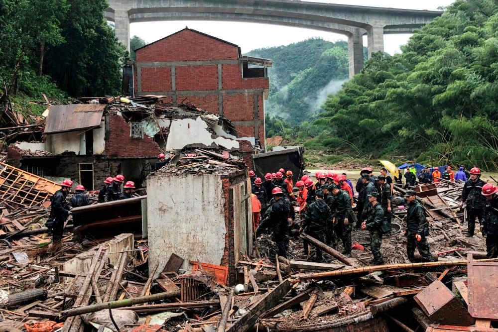 This file photo taken on August 11, 2019 shows rescuers and paramilitary police officers searching in the rubble of damaged buildings after torrential rain caused by Typhoon Lekima, at Yongjia, in Wenzhou, in China's eastern Zhejiang province. - AFP