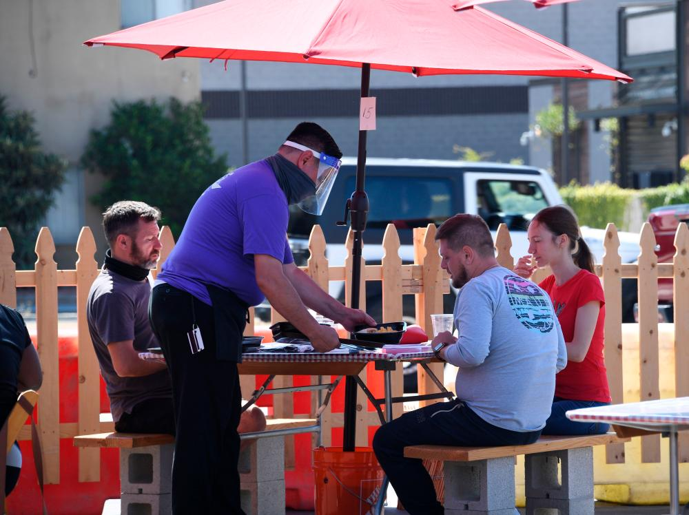 A waiter serves food to customers on the patio at Pann's, an iconic Los Angeles, California, restaurant and coffee shop, on July 4. Spending on services increased in the third quarter of 2020, thought it remained below its fourth quarter 2019 level. – AFPPIX