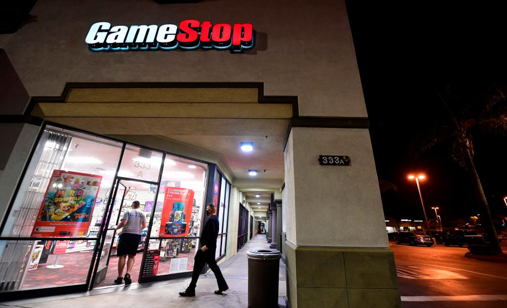 People enter a GameStop store in Alhambra, California, on Wednesday. An epic battle is unfolding on Wall Street, with a cast of characters clashing over the fate of GameStop, a struggling chain of video game retail stores. – AFPPIX
