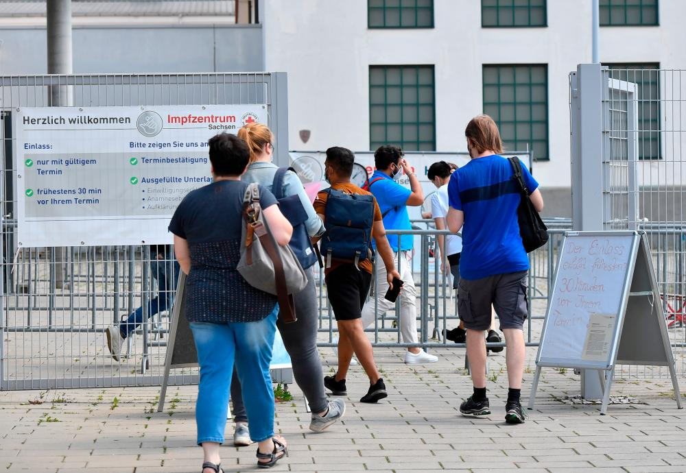 People line up to receive the vaccine against coronavirus disease (Covid-19) at a vaccination center at the Dresden Fair, in Dresden, Germany, July 29, 2021. — Reuters