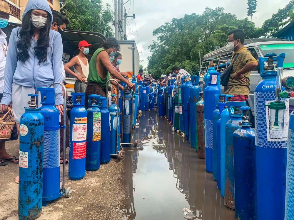 People stand with empty oxygen canisters as they wait to fill them up outside a factory in Yangon on 11 July - AFP via Getty images