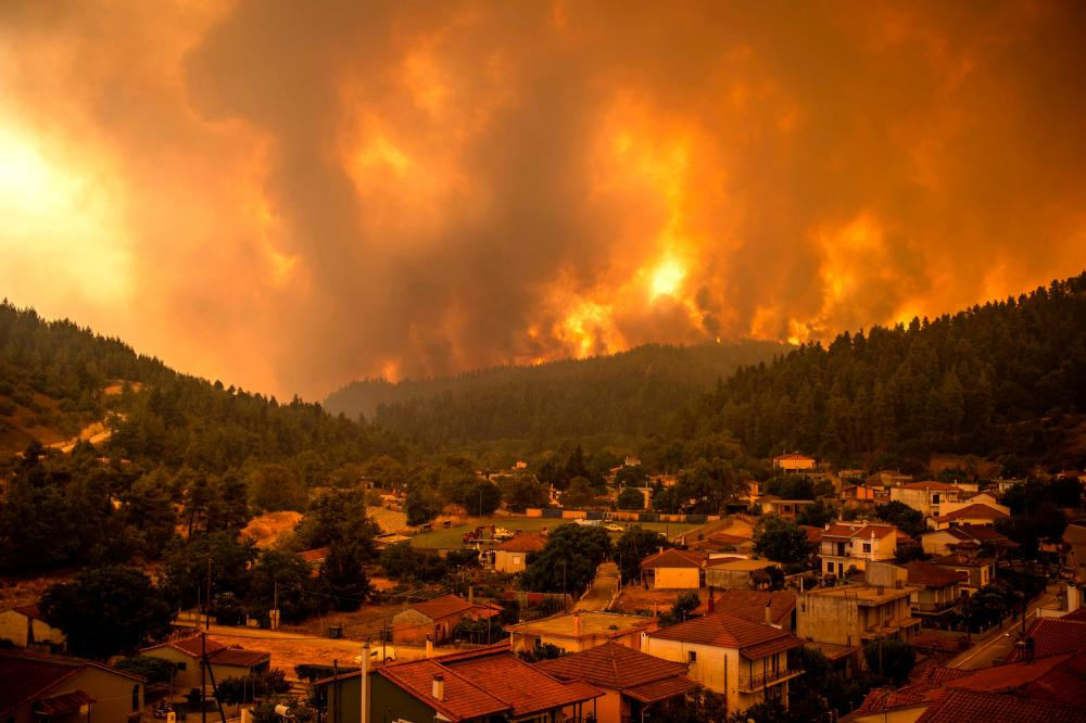 This picture taken on Evia (Euboea) island, second largest Greek island, on August 8, 2021 shows a wildfire moving towards the village of Gouves. — AFP