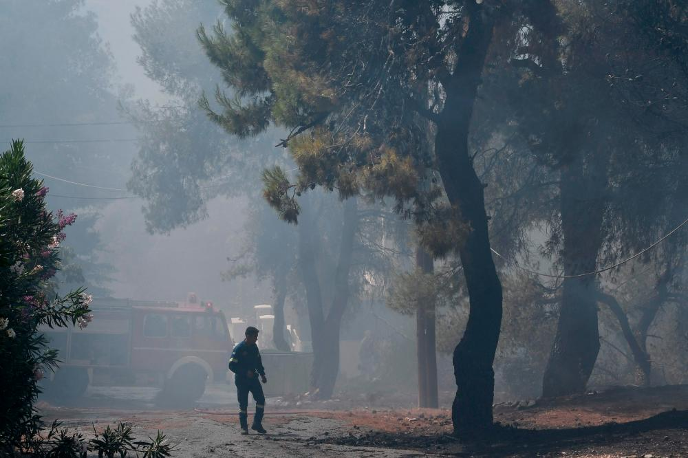 A man walks past a firefighters' truck during a forest fire in Dionysos, north east of Athens, on July 27, 2021. -AFP