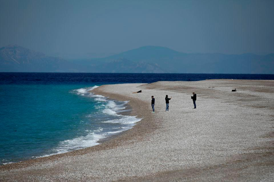 People stand on Elli Beach, amid the coronavirus disease (Covid-19) pandemic, on the island of Rhodes, Greece, April 12, 2021. — Reuters/File Photo