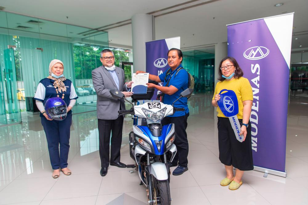 A joyful moment - Mohammad Azhar (in blue) receiving his Modenas CT 115S from Mahmood Abd Razak, Group Head of Strategic Communications of DRB-HICOM. The handing over ceremony was witnessed by Balkish Hood, Head of Marketing and Communications at MODENAS (L) and Angie S Chin, the CEO and Co-founder of Hanafundme.com (R).