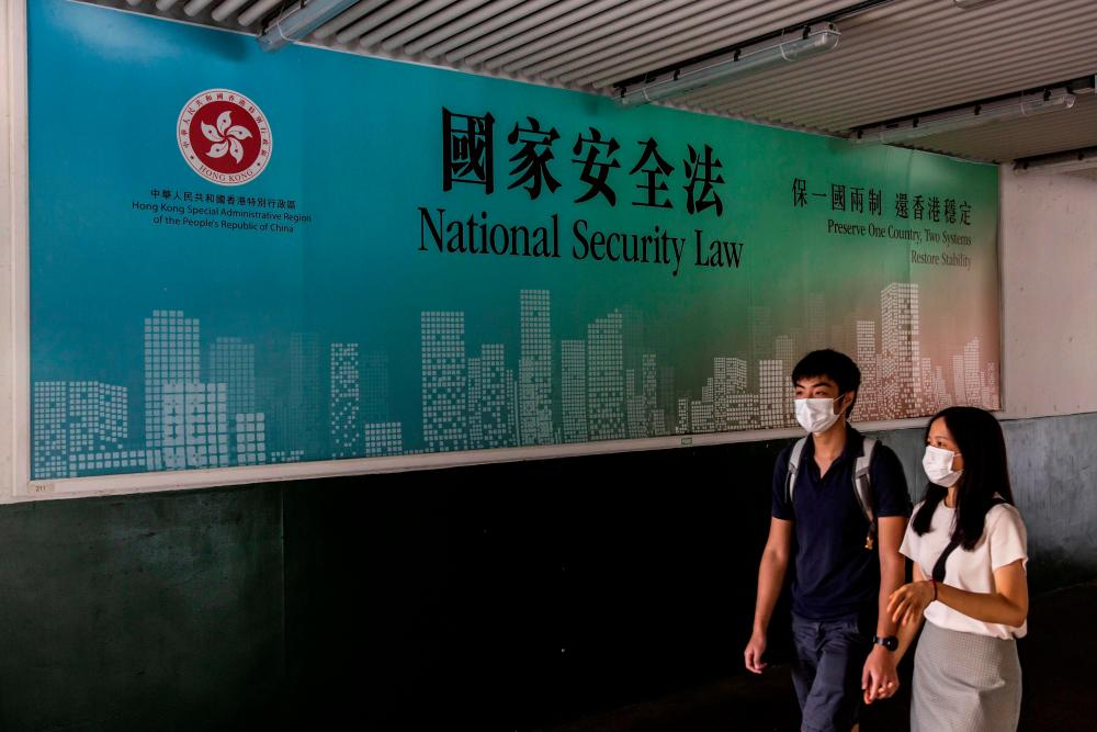 A couple walks past a government advertisement promoting Chinas new national security law in Hong Kong on July 18, 2020. — AFP