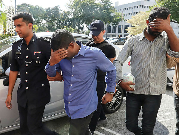 The two famous nasi kandar restaurant staff in Bukit Jambul being led by police to obtain a 7 day remand order against them after lodging false police report that the eatery's three day's takings worth RM122,555 were robbed by armed robbers — Sunpix by Masry Che Ani