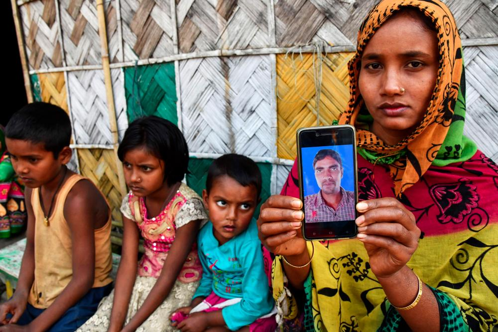 In this picture taken on Dec 30, 2018, Sajeda Khatun, wife of Saher Islam, who is still trapped after an illegal coal mine became flooded on Dec 13, shows her husband's photograph on her mobile phone as she sits with her children at her house in Bhangmari village in Chirang district of Assam. — AFP
