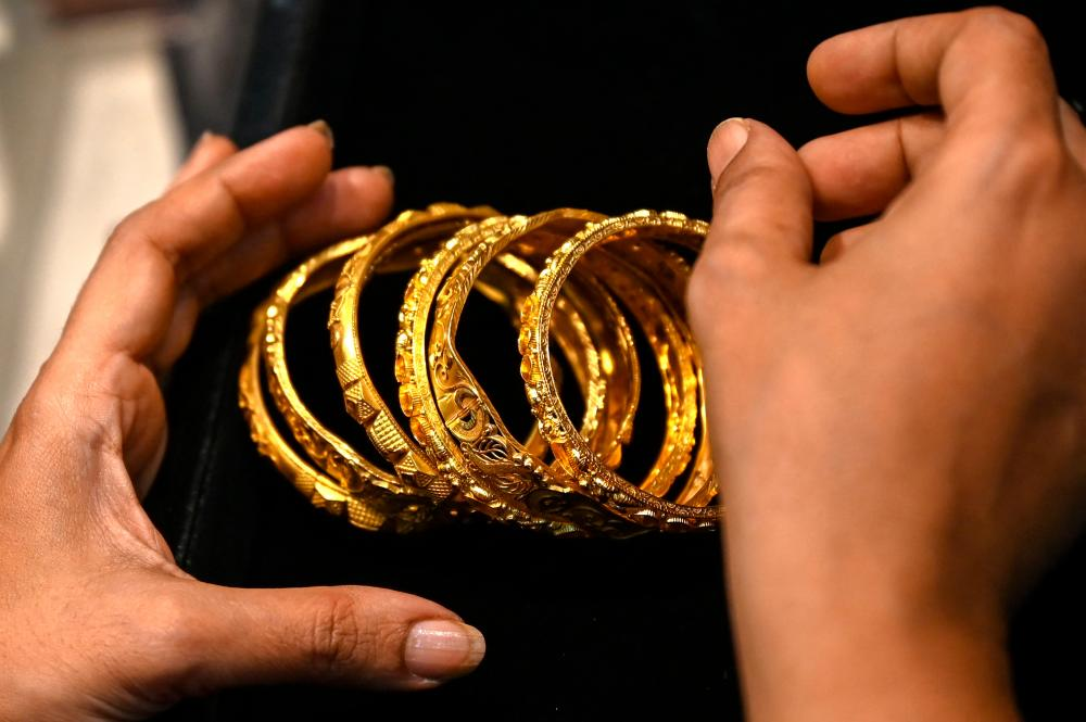 This picture taken on August 11, 2021 shows a customer handling gold bracelets at a jewellery shop in Mumbai. AFPpix