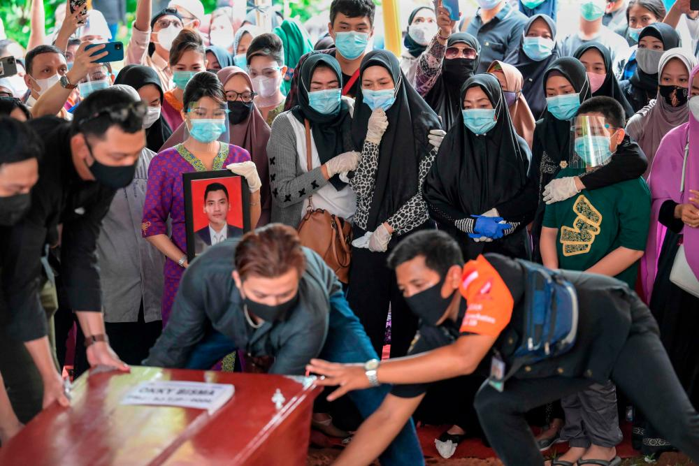 Aldha Refa (centre R-spotted top), the wife of Okky Bisma, a flight attendant and one of the 62 people aboard Sriwijaya Air flight SJ182 which crashed shortly after takeoff on January 9, looks toward the coffin with family members as they attend his funeral in Jakarta on January 14, 2021. / AFP / BAY ISMOYO