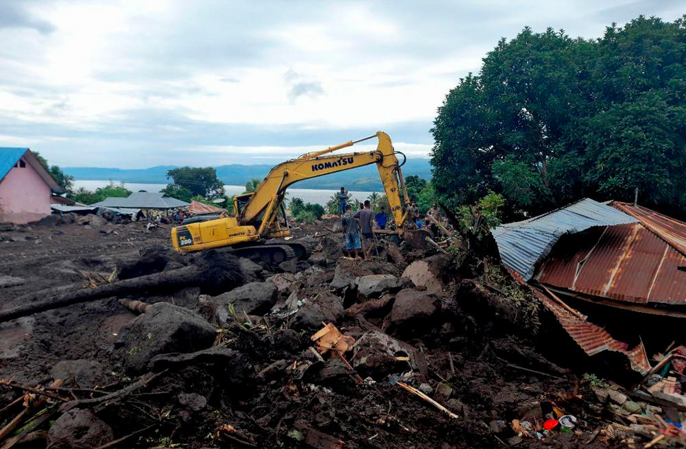 This picture taken on April 7, 2021 shows rescuers using diggers and shovels to extract mud-covered corpses from the debris in Lamanele village, East Flores, after torrehtial rains from Tropical Cyclone Seroja, one of the most destructive storms to hit the region in years, turned small communities into wastelands of mud. –AFP