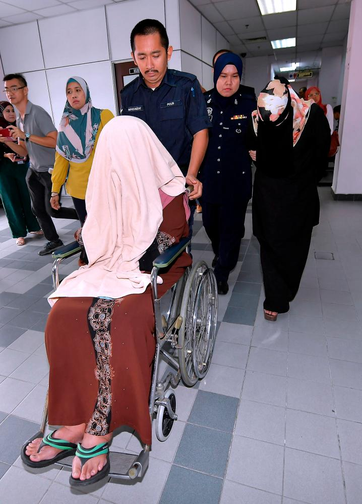 Ledang district health officer Dr Zaharah Mohda Salleh, 59, (front) and assistant accountant Noor Shazriena Miskam, 34, (R) were charged in the Johor Baru sessions court today on 49 charges of corruption. - Bernama