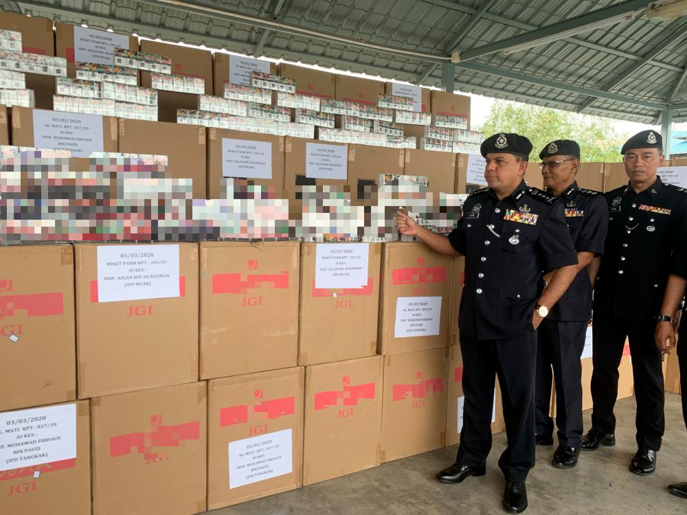 Johor police chief Datuk Ayob Khan Mydin Pitchay (3rd from R) displays some of the seized cigarettes worth a total of RM3.2 million, at a press conference at the Muar PPM base today. - Bernama