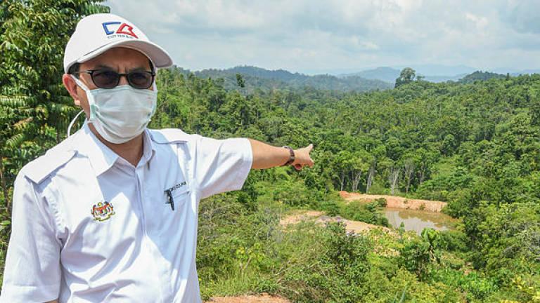 Deputy Minister of Water, Land and Natural Resources Tengku Zulpuri Shah Raja Puri points to the reservoir water from an iron ore mine near a Orang Asli settlement, while visiting the Batek Orang Asli community in Kampung Kuala Koh on June 9, 2019. — Bernama