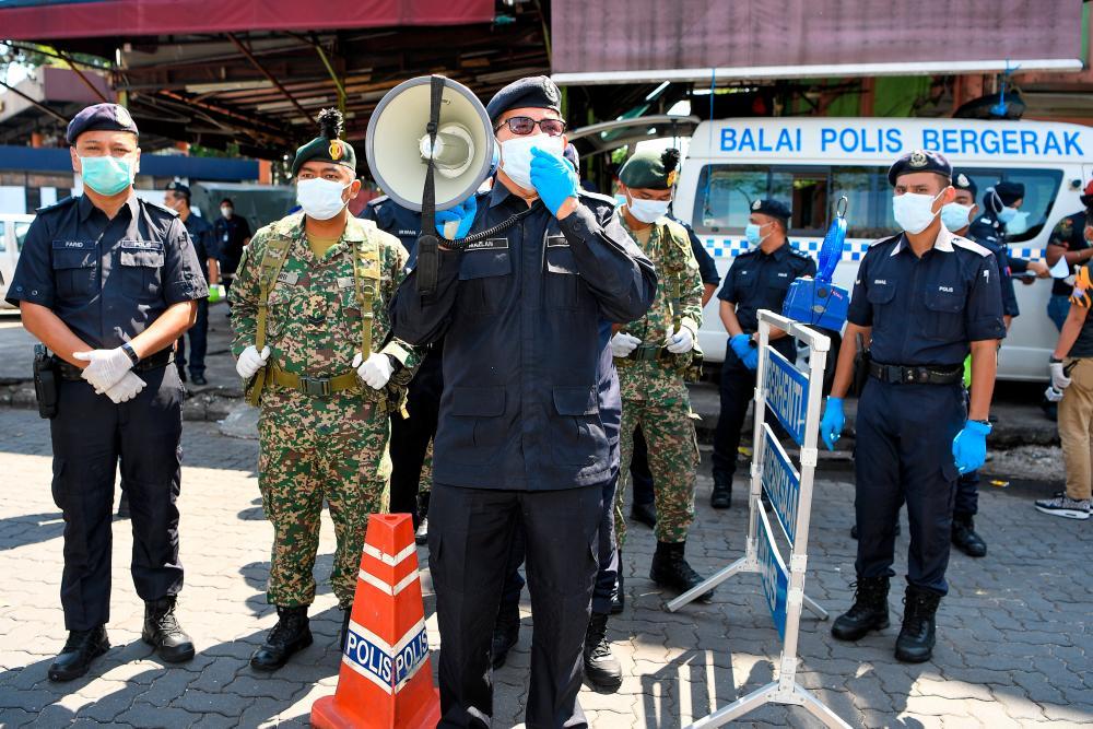 Kuala Lumpur Police Chief Datuk Seri Mazlan Lazim (C) issues instructions on the MCO at the Kuala Lumpur wholesale market today. - Bernama