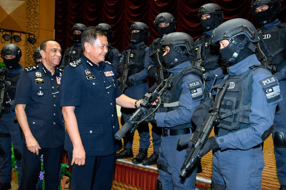 IGP Tan Sri Abdul Hamid Bador and Bukit Aman NCID director Datuk Khalil Kader Mohd (2nd from L) have a friendly chat with NCID members during the launch of the departments corporate video and theme song at the Police Officers' College in Cheras today. - Bernama