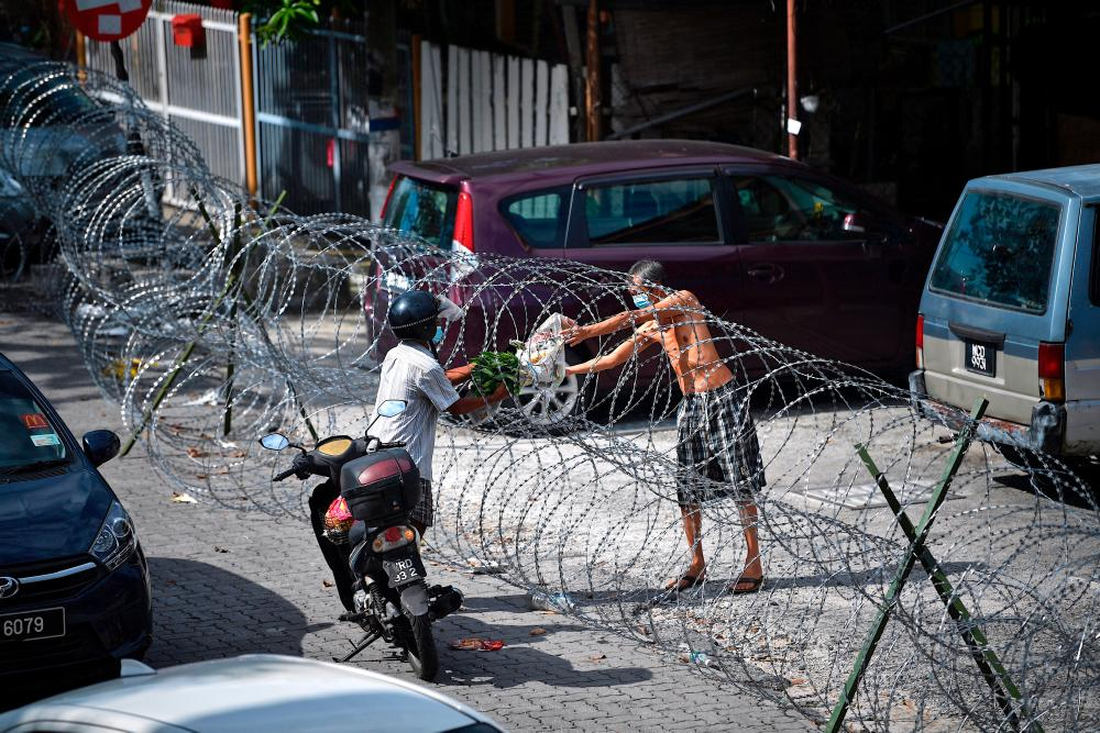 A resident of Selayang Baru collects his delivery through barbed wires, on May 4, 2020. — Bernama